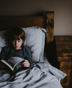 boy in bed with book